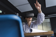 Young woman wearing VR glasses at table in office - UUF12844