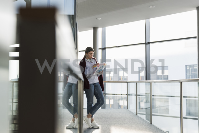 Young woman standing at the window reading document - UUF12847