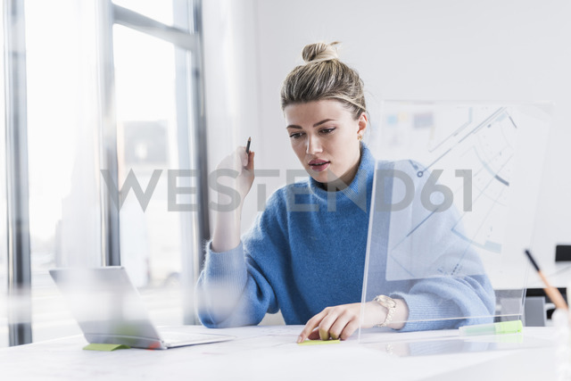 Young woman with laptop and transparent design working on plan at desk in office - UUF12850