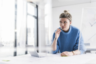 Young woman with laptop at desk in office thinking - UUF12853