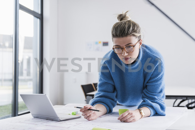 Young woman with laptop working on plan at desk in office - UUF12856
