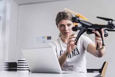 Young woman with laptop at desk holding drone - UUF12862