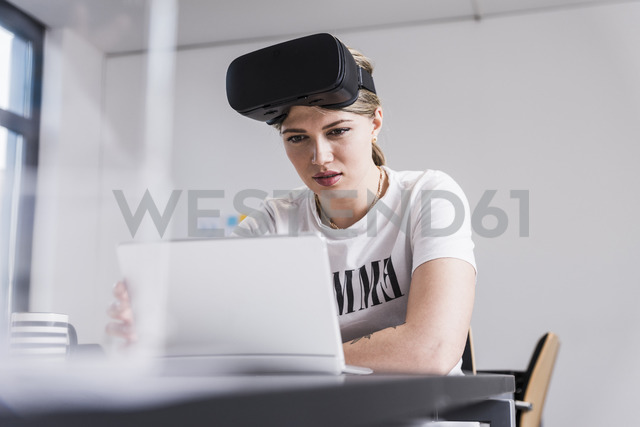 Young woman with laptop and VR glasses working at desk in office - UUF12865