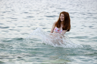 Italy, happy teenage girl splashing in the sea - LBF01802