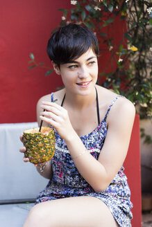 Smiling young woman drinking a cocktail in pineapple outdoors - LFEF00063