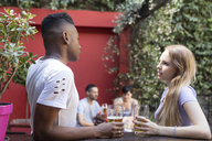 Young couple talking having a beer at outdoor bar - LFEF00066