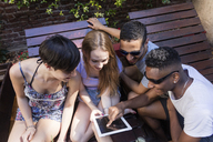 Happy friends sharing tablet outdoors - LFEF00069