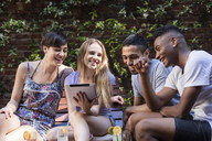 Happy friends with cocktails sharing tablet outdoors - LFEF00072