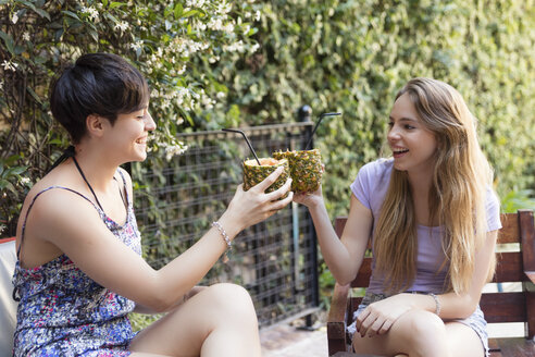 Happy friends toasting with cocktails in pineapples outside - LFEF00078