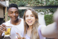 Smiling young couple having a beer and taking a selfie outdoors - LFEF00087