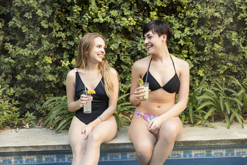 Two happy young women drinking cocktails at the edge of a swimming pool - LFEF00096