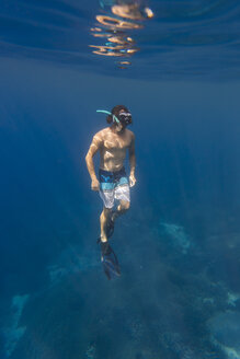 Man with fins and snorkel diving under water - KNTF01026