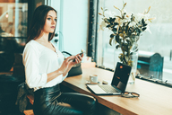 Pensive young businesswoman using smartphone in a coffee shop - OCAF00159
