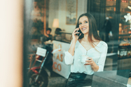 Portrait of happy young woman on the phone in a coffee shop - OCAF00162