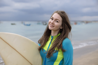 Indonesia, Bali, young woman with surf board - KNTF01039