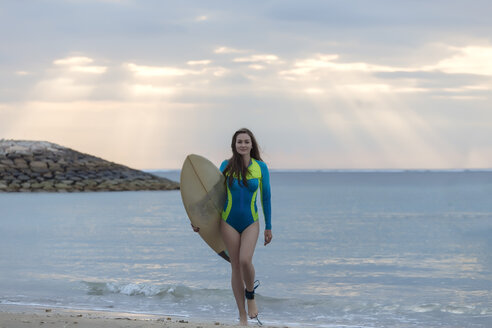 Indonesia, Bali, young woman with surf board walking at beach - KNTF01042