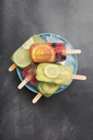 Various fruit popsicles on bowl with ice cubes - SKCF00340