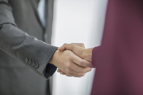 Close-up of businessman and businesswoman shaking hands - ZEF15037