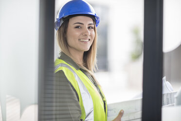 Portrait of smiling woman wearing hard hat and reflective jacket - ZEF15055