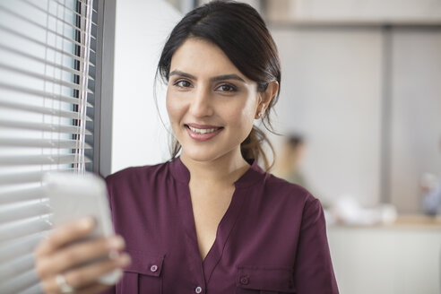 Portrait of smiling businesswoman holding cell phone in office - ZEF15058