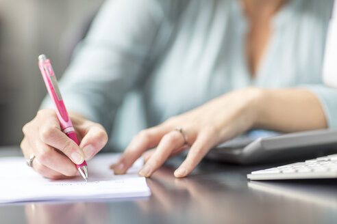 Woman at desk in office taking notes - ZEF15087