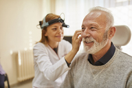 ENT physician examining ear of a senior man - ZEDF01232