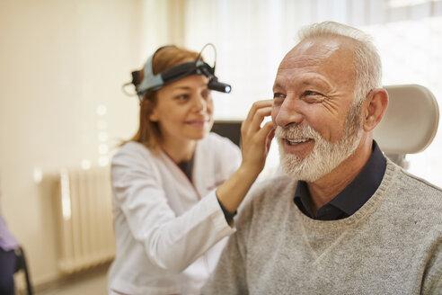 ENT physician examining ear of a senior man - ZEDF01232