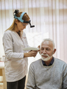 ENT physician examining ear of a senior man - ZEDF01235