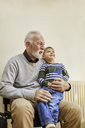 Boy sitting on grandfather's lap in waiting room - ZEDF01241