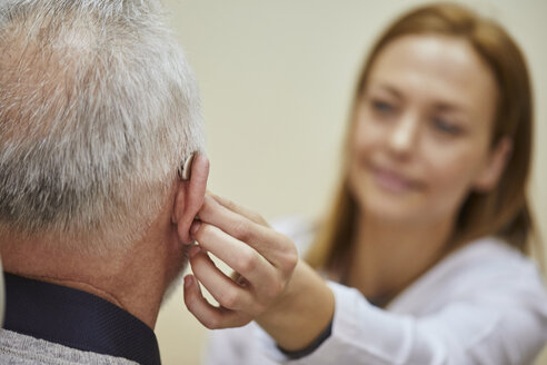 Female doctor applying hearing aid to senior man's ear - ZEDF01253
