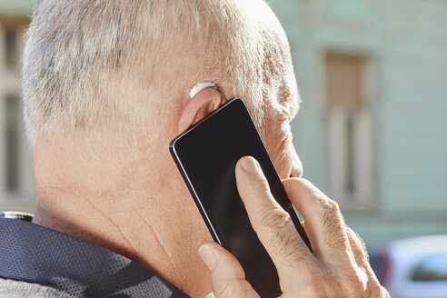 Close-up of senior man with hearing aid using smartphone - ZEDF01256