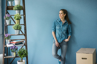 Beautiful woman in her new home, decorated with plants, leaning at wall - MOEF00862