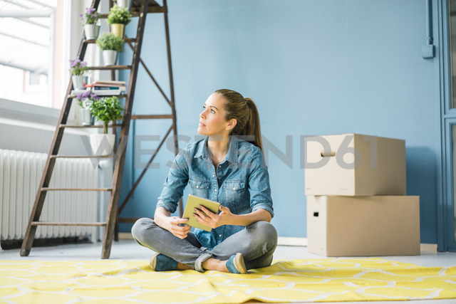Woman sitting on floor of her new apartment, using digital tablet - MOEF00868 - Robijn Page/Westend61