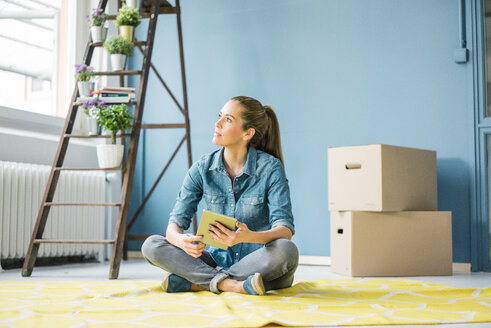 Woman sitting on floor of her new apartment, using digital tablet - MOEF00868