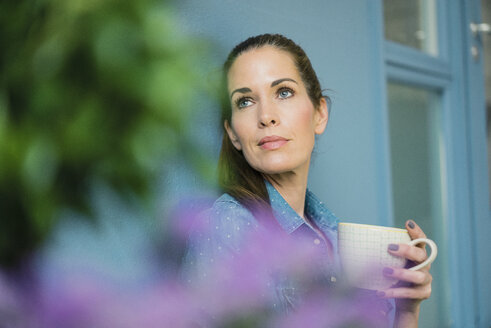 Woman relaxing in her home with potted plants, drinking coffee - MOEF00871