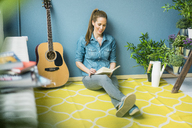 Woman relaxing in her home with potted plants, reading a book - MOEF00877