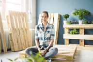 Beautiful woman taking a break from refurbishing her home with pallets, drinking coffee - MOEF00880