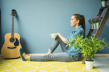 Beautiful woman in her home, decorated with plants, drinking coffee - MOEF00883