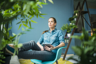 Beautiful woman in her home, decorated with plants - MOEF00886