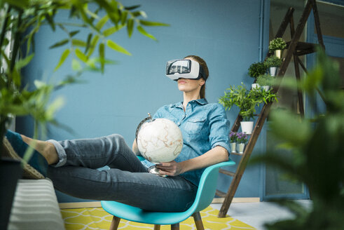 Beautiful woman sitting in her home, decorated with plants, holding globe, wearing VR glasses - MOEF00889