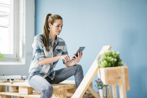 Woman refurbishing her new home with pallets, using digital tablet - MOEF00892