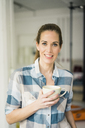 Portrait of a beautiful woman, drinking coffee at home - MOEF00898