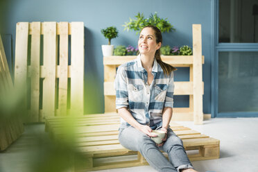 Beautiful woman taking a break from refurbishing her home with pallets, drinking coffee - MOEF00901