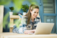 Laughing woman using laptop in hetr new flat - MOEF00904