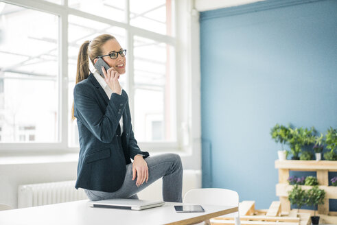Businesswoman working from home, talking on the phone - MOEF00919