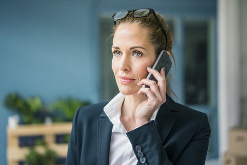 Successful businesswoman standing at home, talking on the phone - MOEF00922