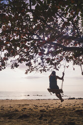 Thailand, Phi Phi Islands, Ko Phi Phi, man on tree swing on the beach - KKAF00892