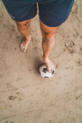 Low section of man with footall on the beach - KKAF00898