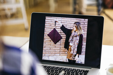 Photo of woman holding bag on laptop screen - JRFF01567