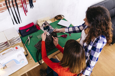 Two fashion designers in studio looking at photography - JRFF01576